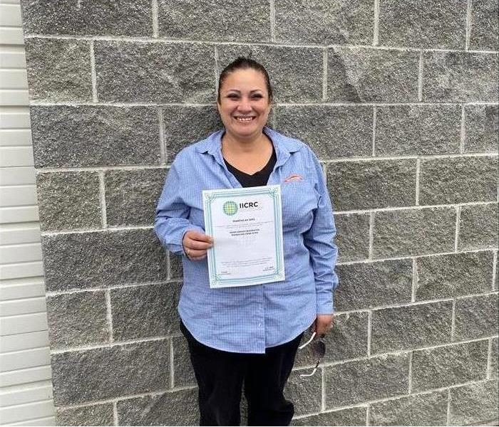 woman in Servpro uniform standing with IICRC Certification in hand